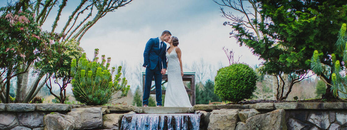 Newlyweds kiss by a beautiful waterfall
