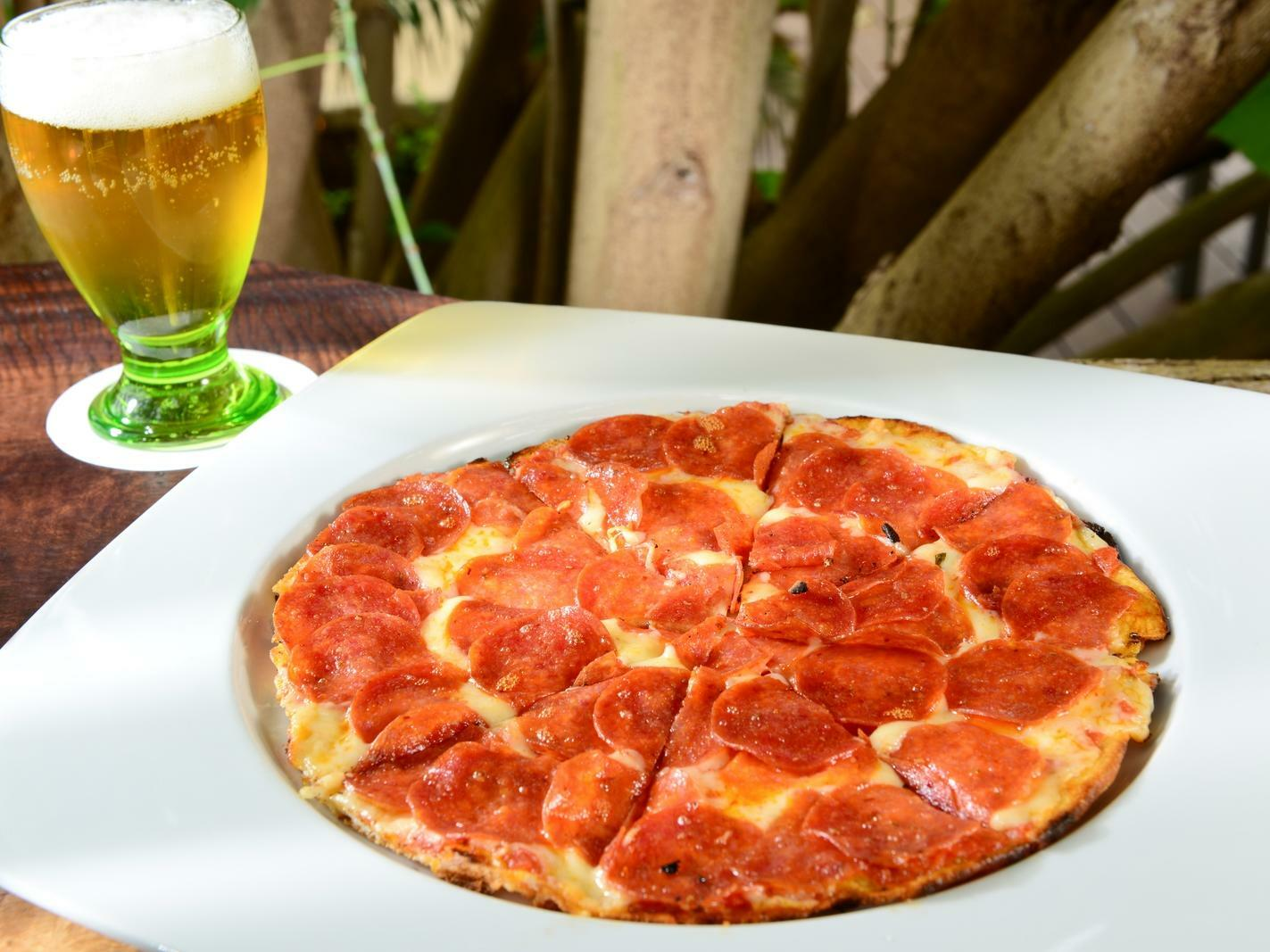 pizza on a white plate with beer glass
