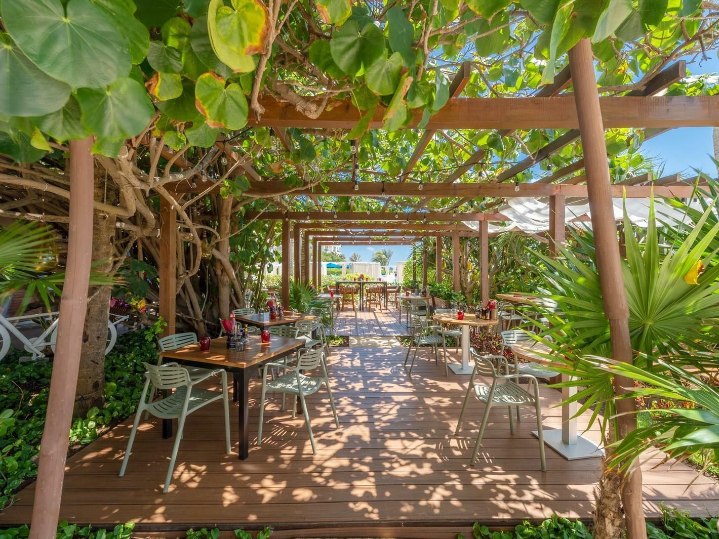 outdoor dining tables under tree covered pergola