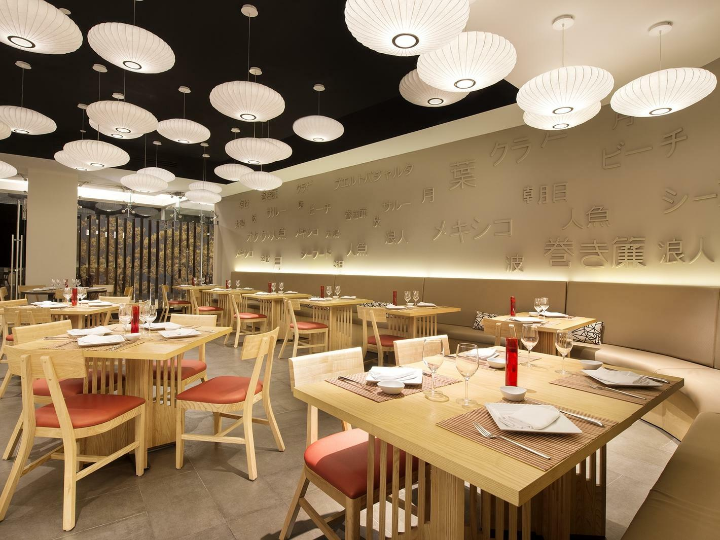 Wooden restaurant dining tables with red  accents at Yuu at Grand Fiesta Americana Puerto Vallarta All Inclusive Adults Only