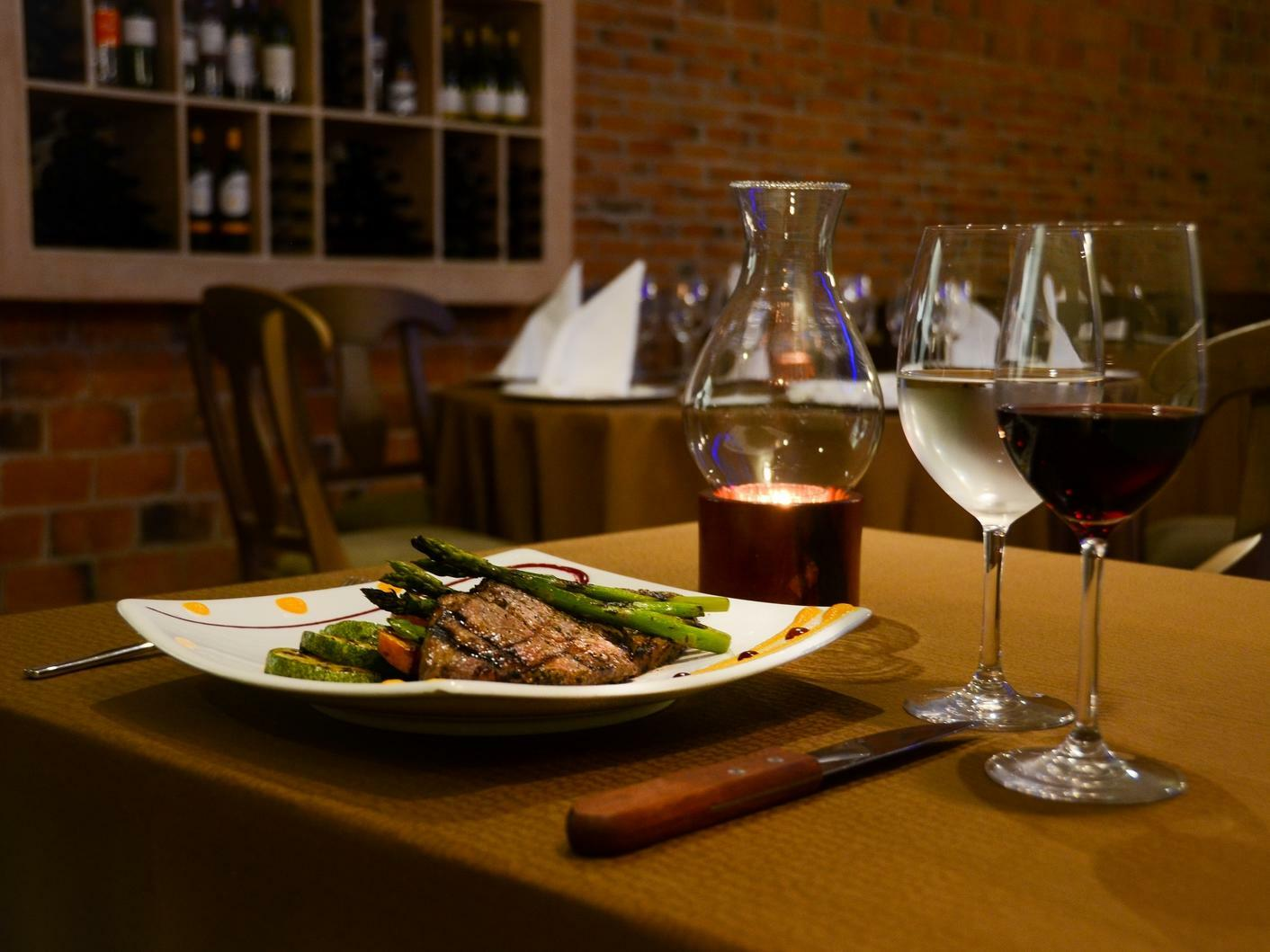 steak and vegetables on a plate next to wine glasses