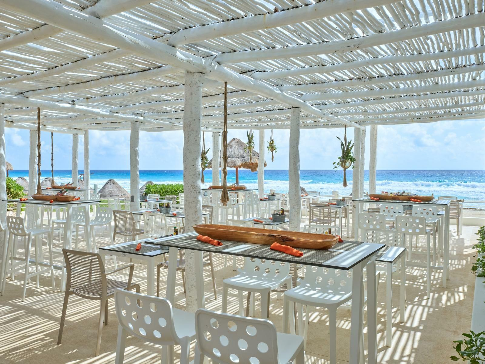 outdoor restaurant with glass tables, white chairs and ocean view