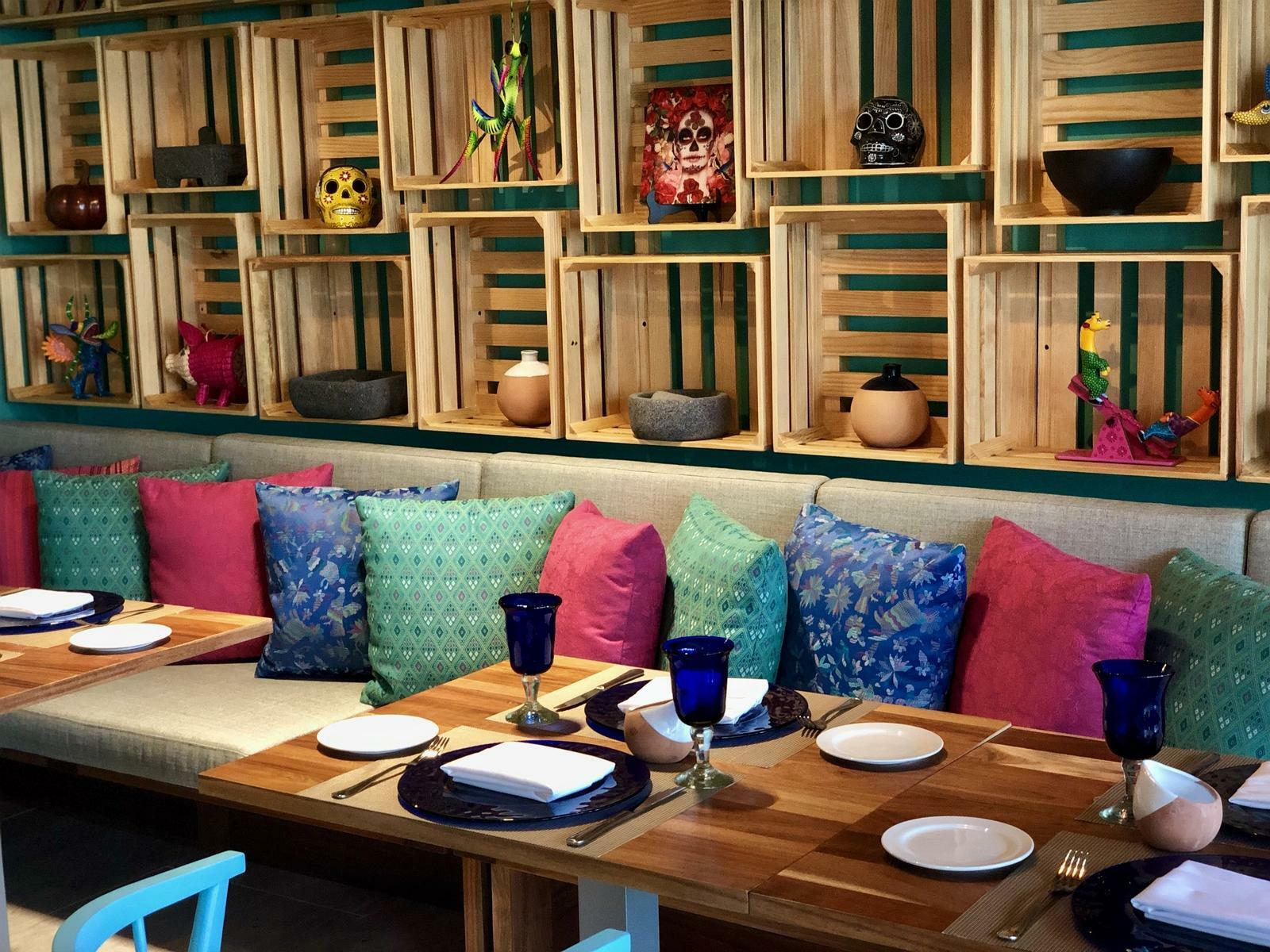 dining booth with colorful pillows and wall accessories