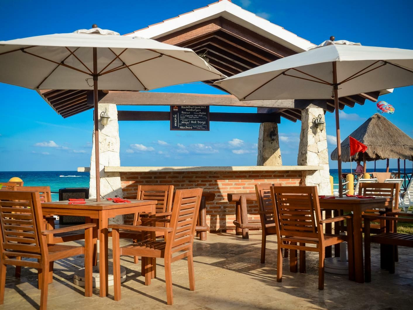 outdoor bar with dining tables and umbrellas
