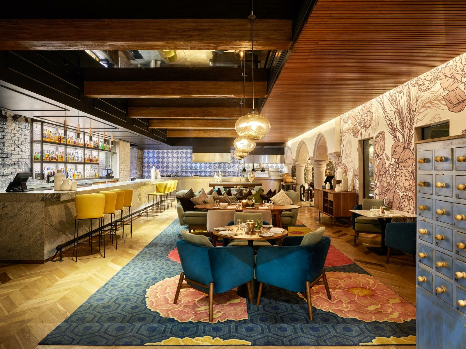 restaurant dining room with tables chairs and blue rug