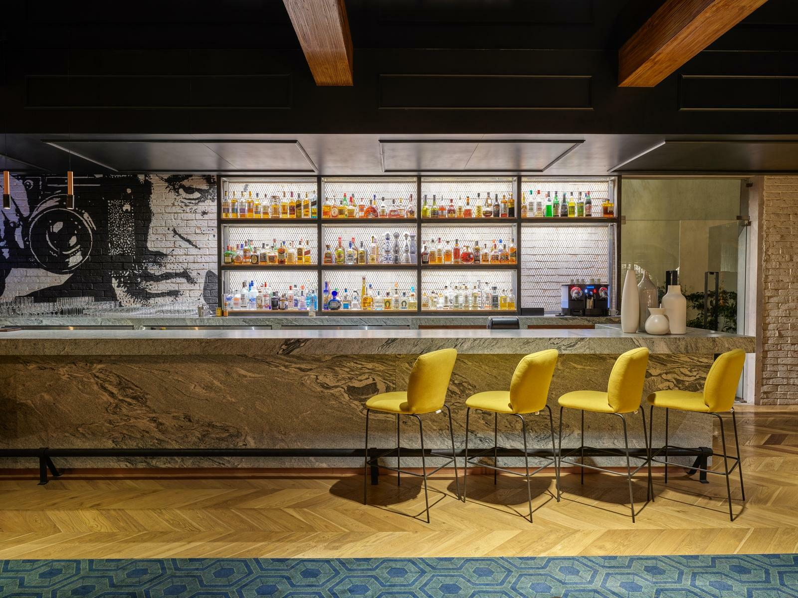 bar with yellow bar stools and liquor bottles on shelves