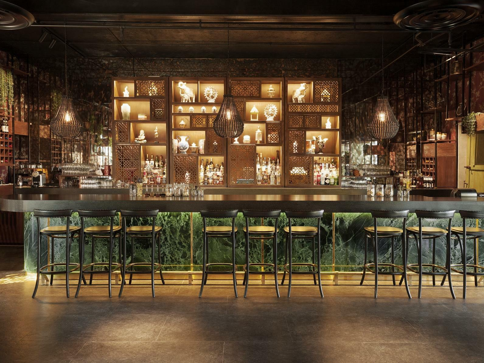 bar with bar stools and liqour bottles on shelves