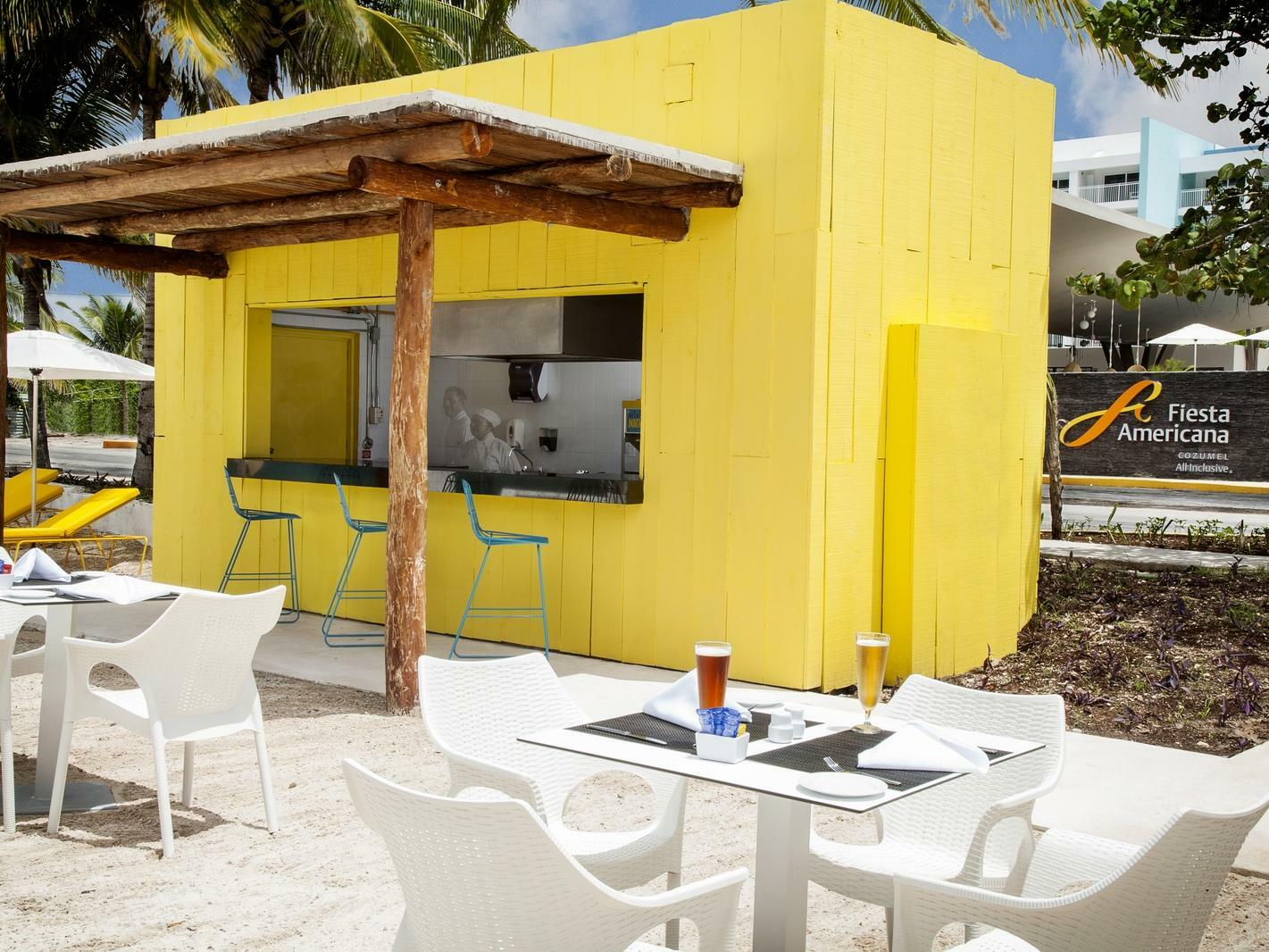 small yellow bar with canopy roof and white dining tables