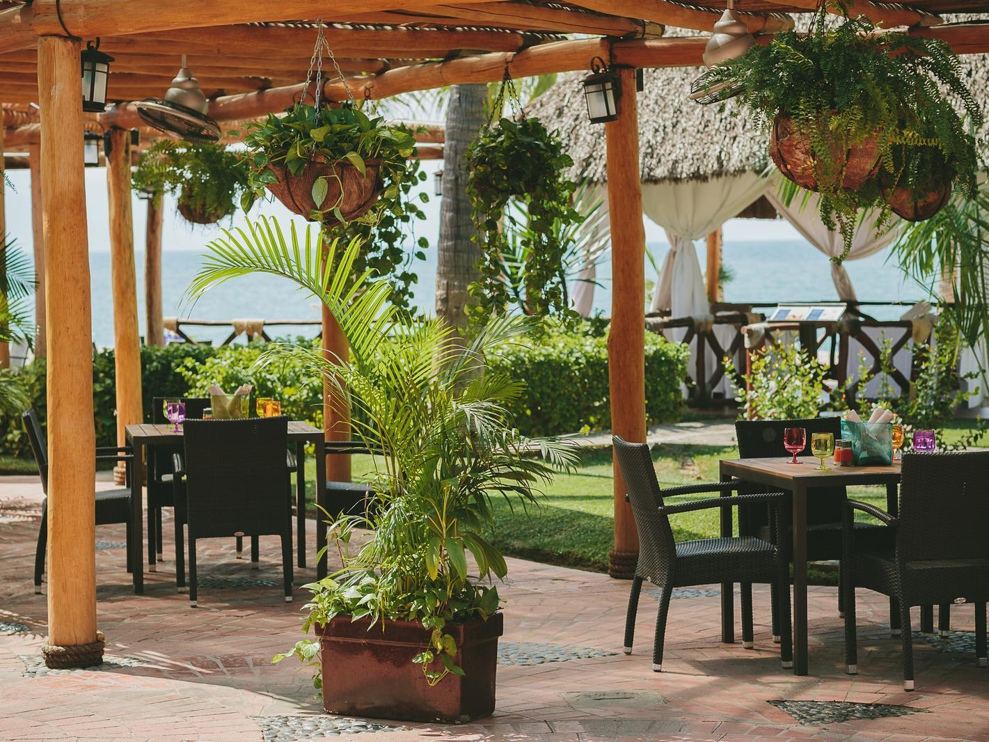 outdoor dining tables with plants hanging above