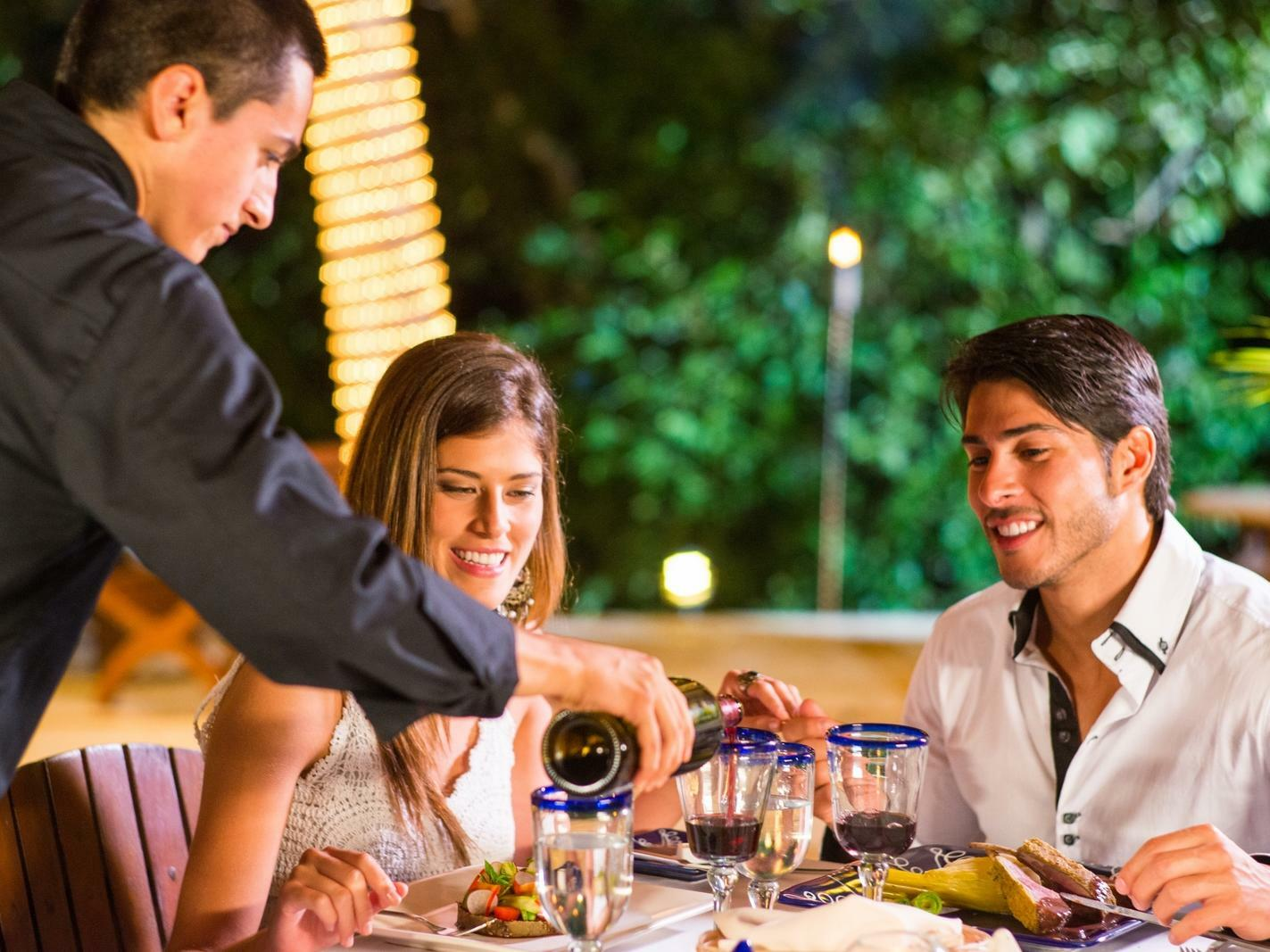 couple being served wine by server