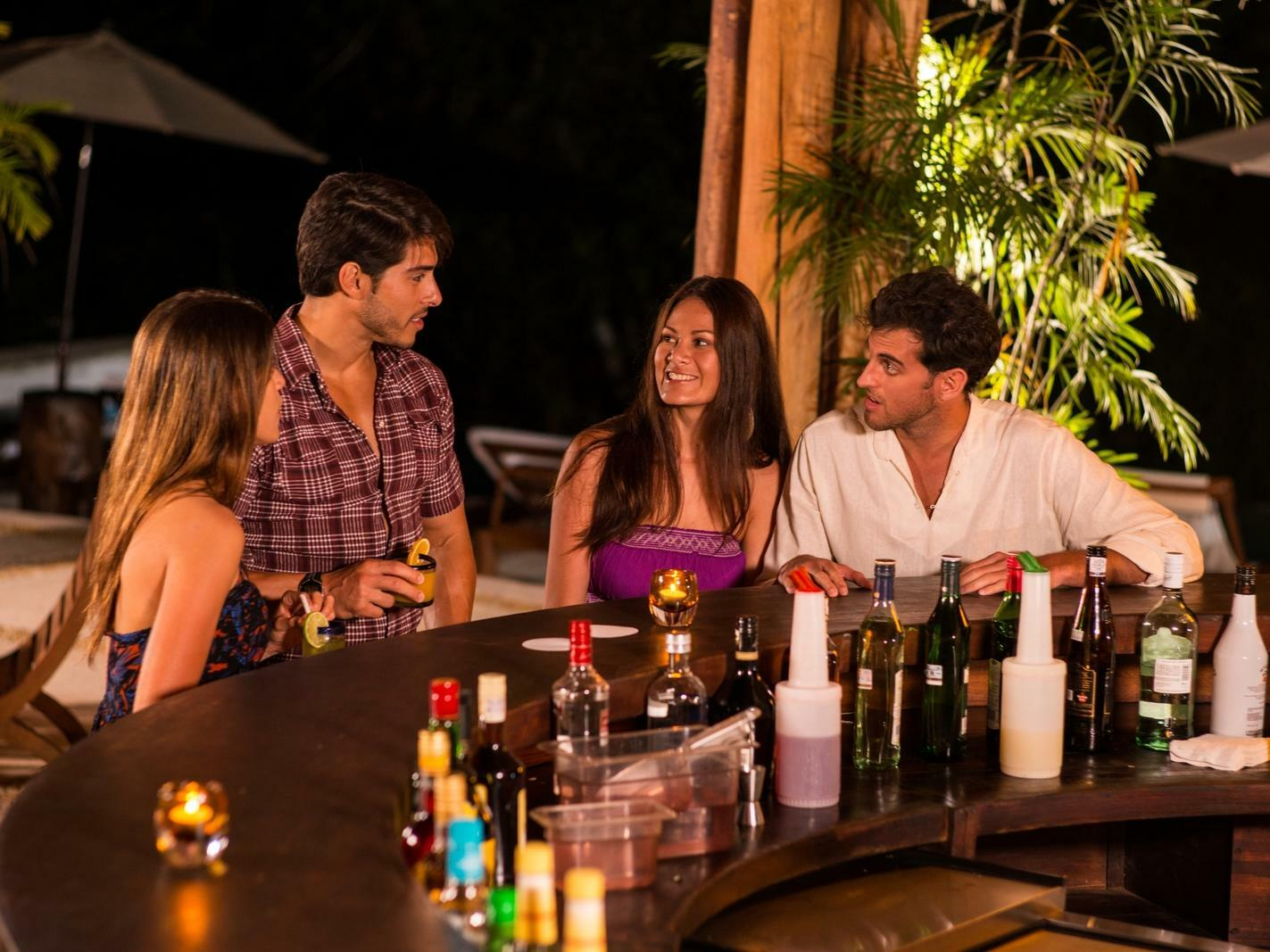two couples conversing at bar