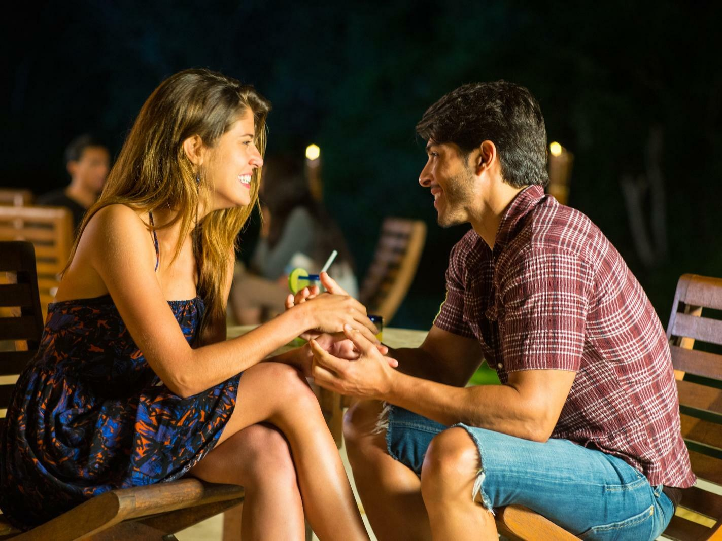 couple holding hands while sitting on small table
