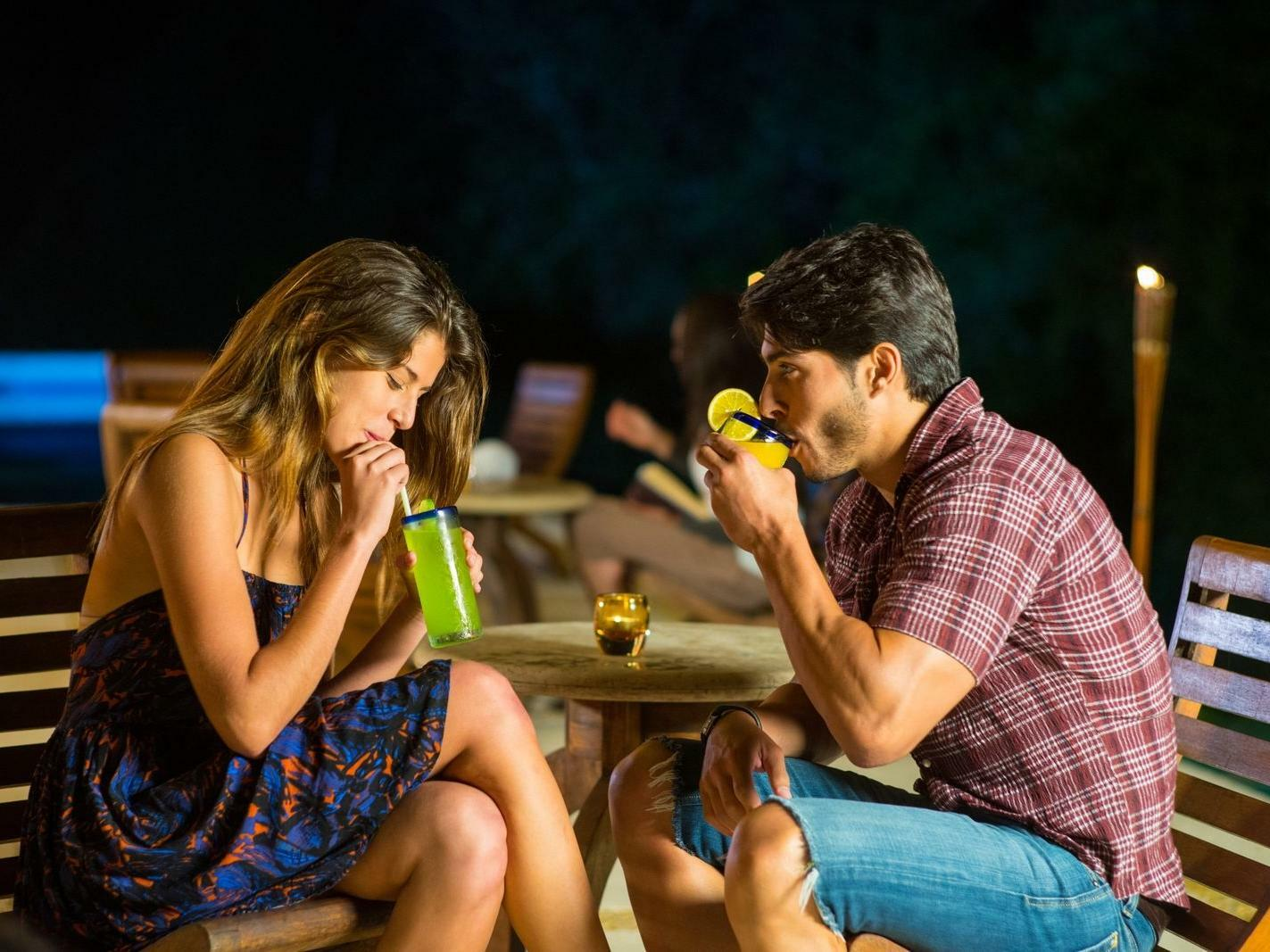 couple sitting at small table drinking cocktails
