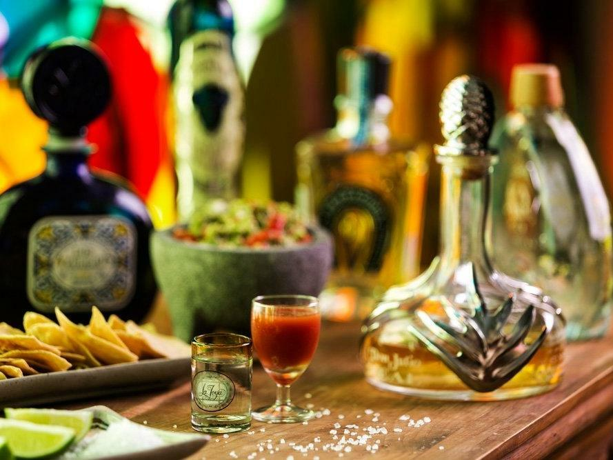 bar with tequila bottles and chips and salsa