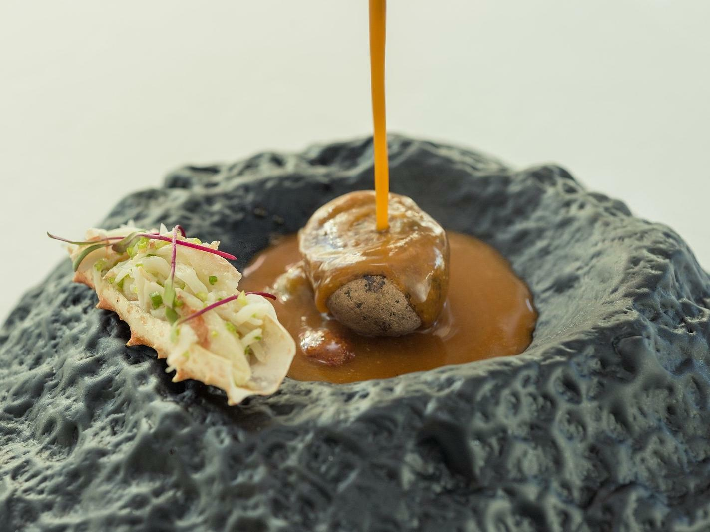 artfully plated food with sauce being drizzled over food