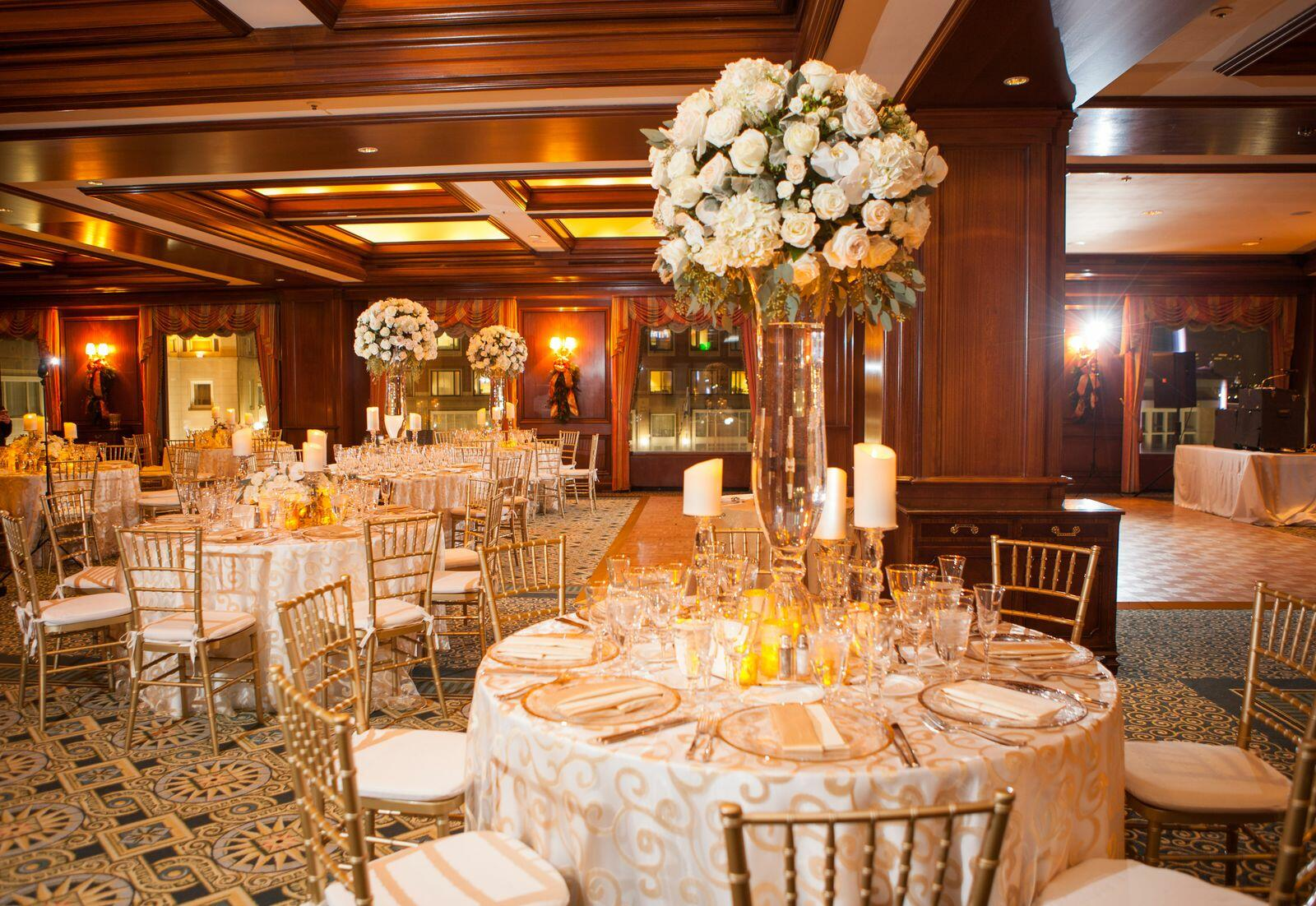 Event space set for wedding reception with large floral centerpi