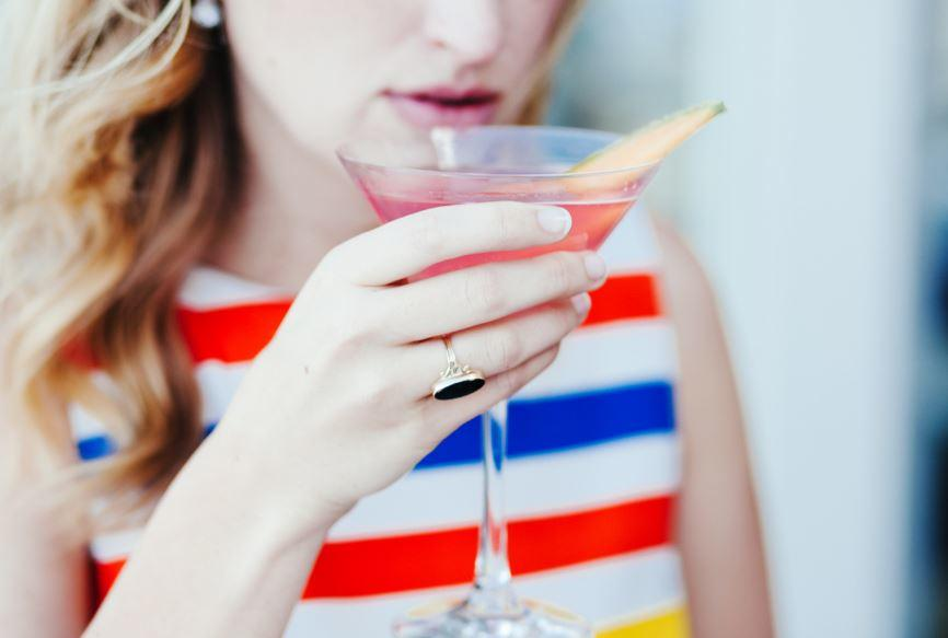 Girl in striped shirt sipping martini
