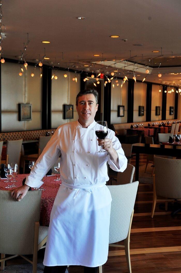 Chef Daniel Bruce holding a glass of wine