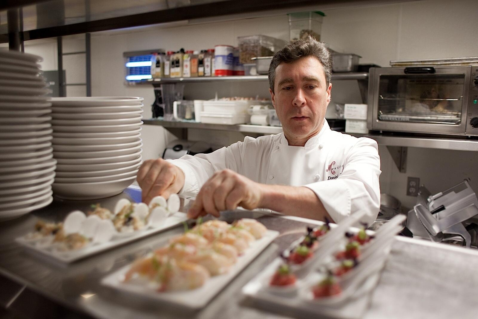 Chef Daniel Bruce in the kitchen observing hors d'oeuvres