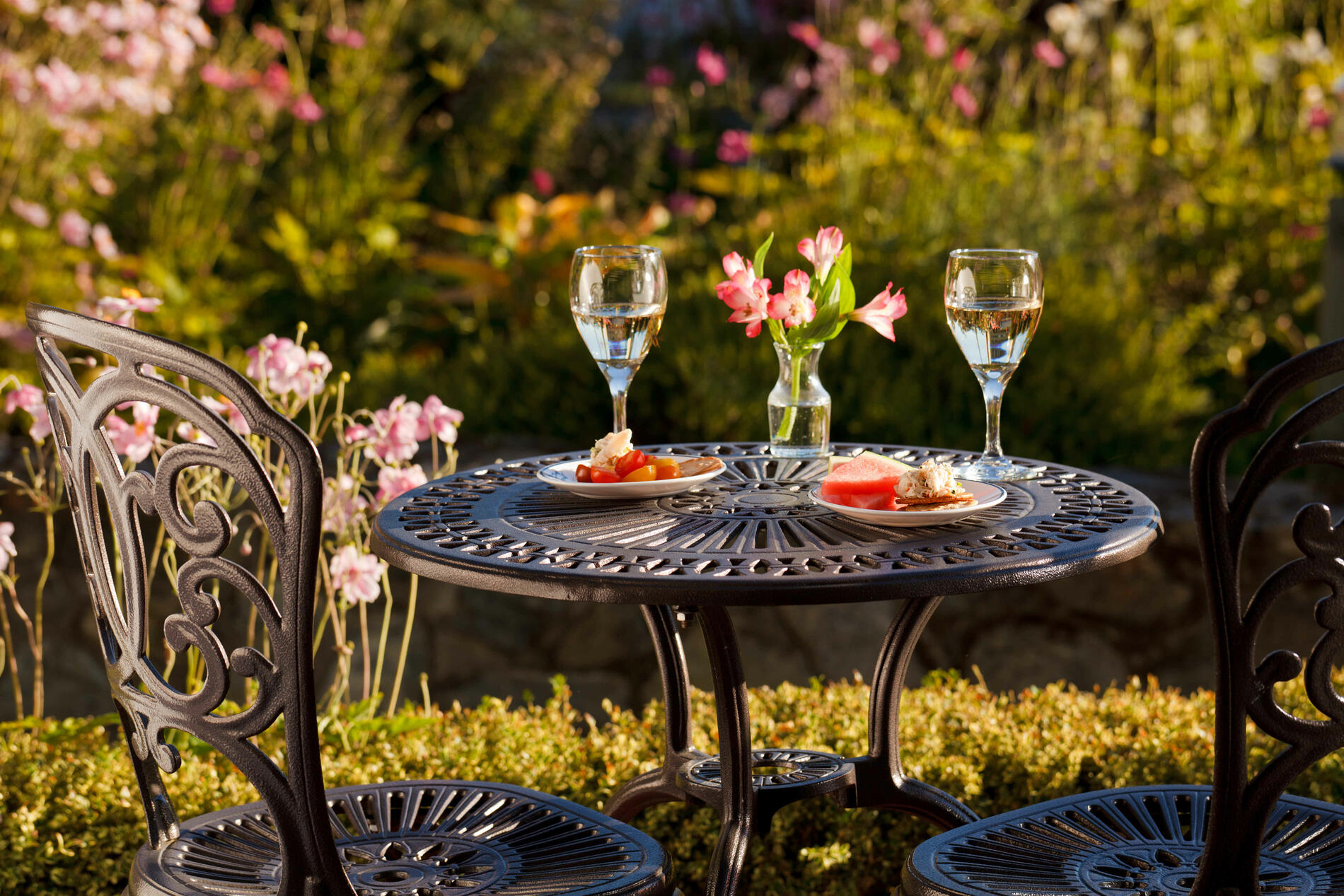Glasses of wine and small plates on wrought iron bistro set