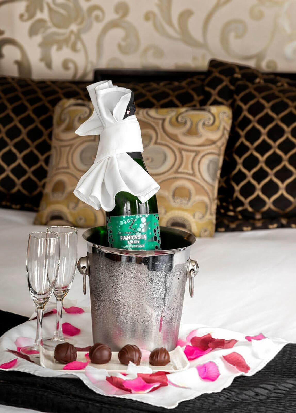 Bottle of champagne in ice bucket with two glasses and chocolate