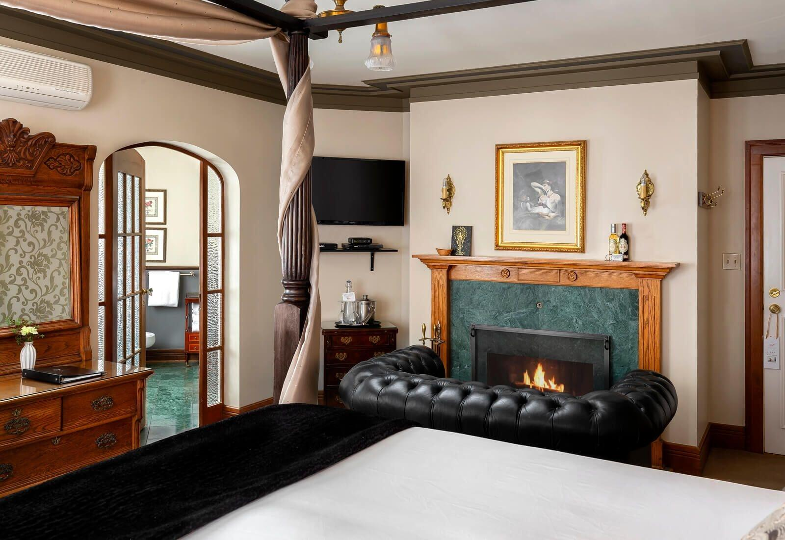 Four post bed with loveseat by fire place