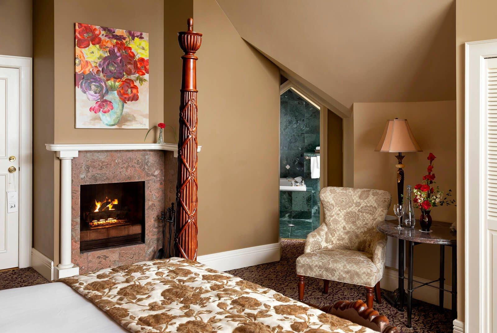 Four post bed with fire place and chair in corner