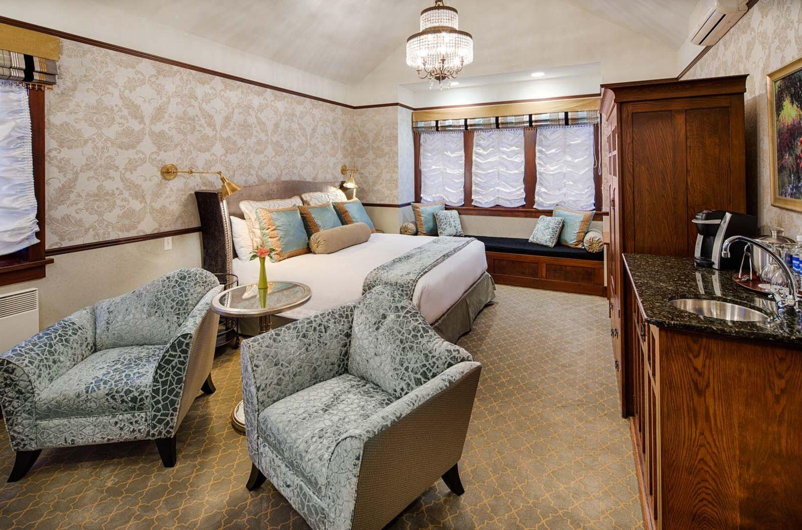 Two accent chairs by wet bar and king bed