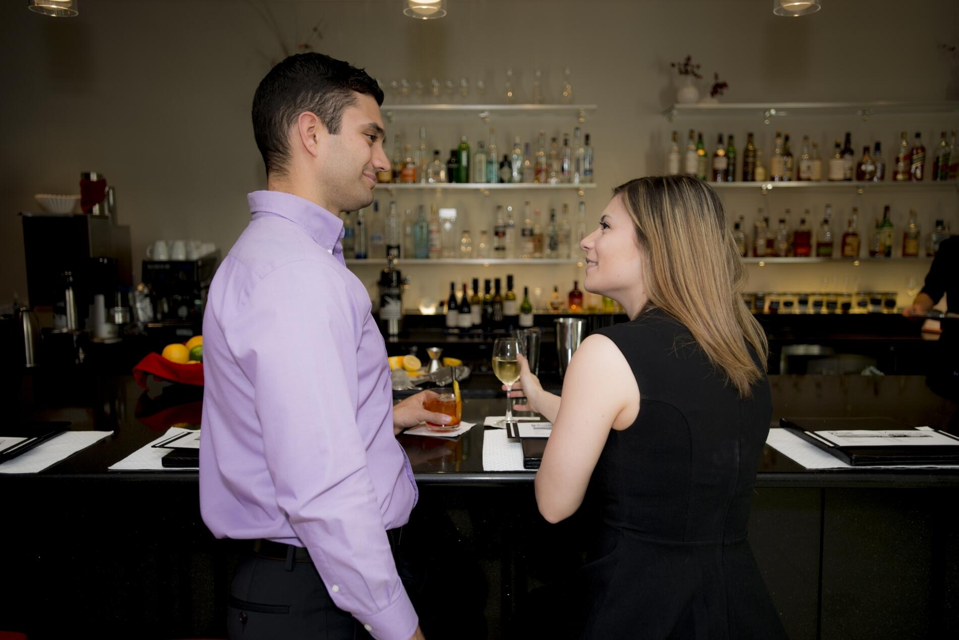 Couple laughing and sipping cocktails at the Maikka Lobby Bar