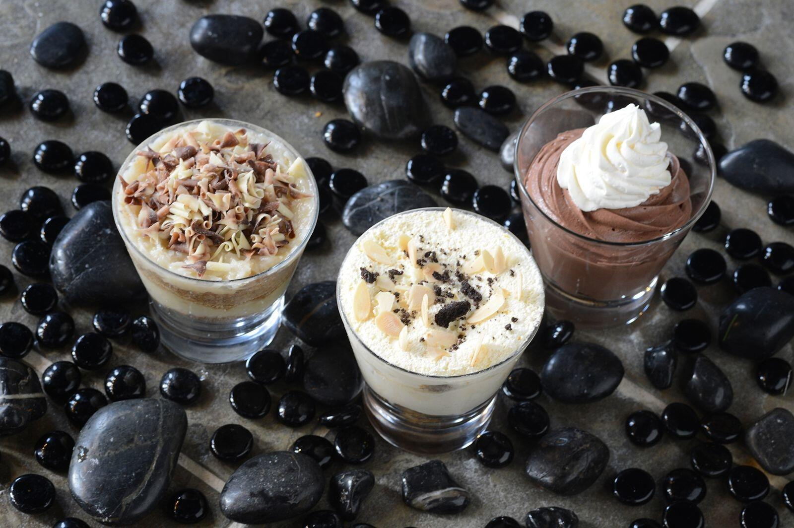 Three dessert shooters artfully surrounded by black pebbles