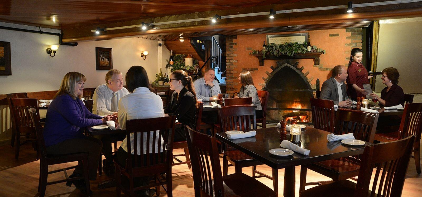 Tables of happy guests eating beside a fireplace