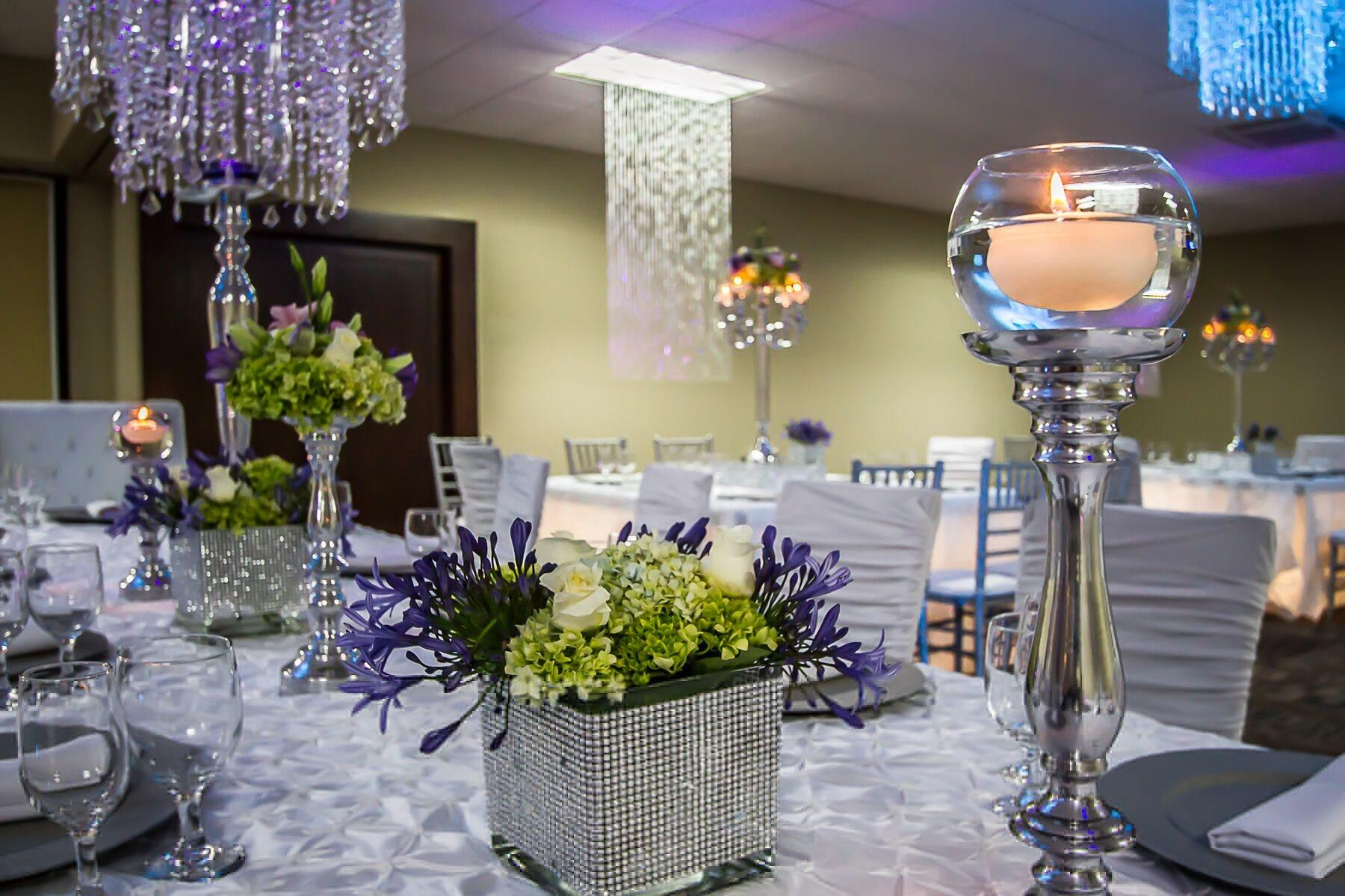 Floral centerpiece and candlesticks on table set for wedding rec