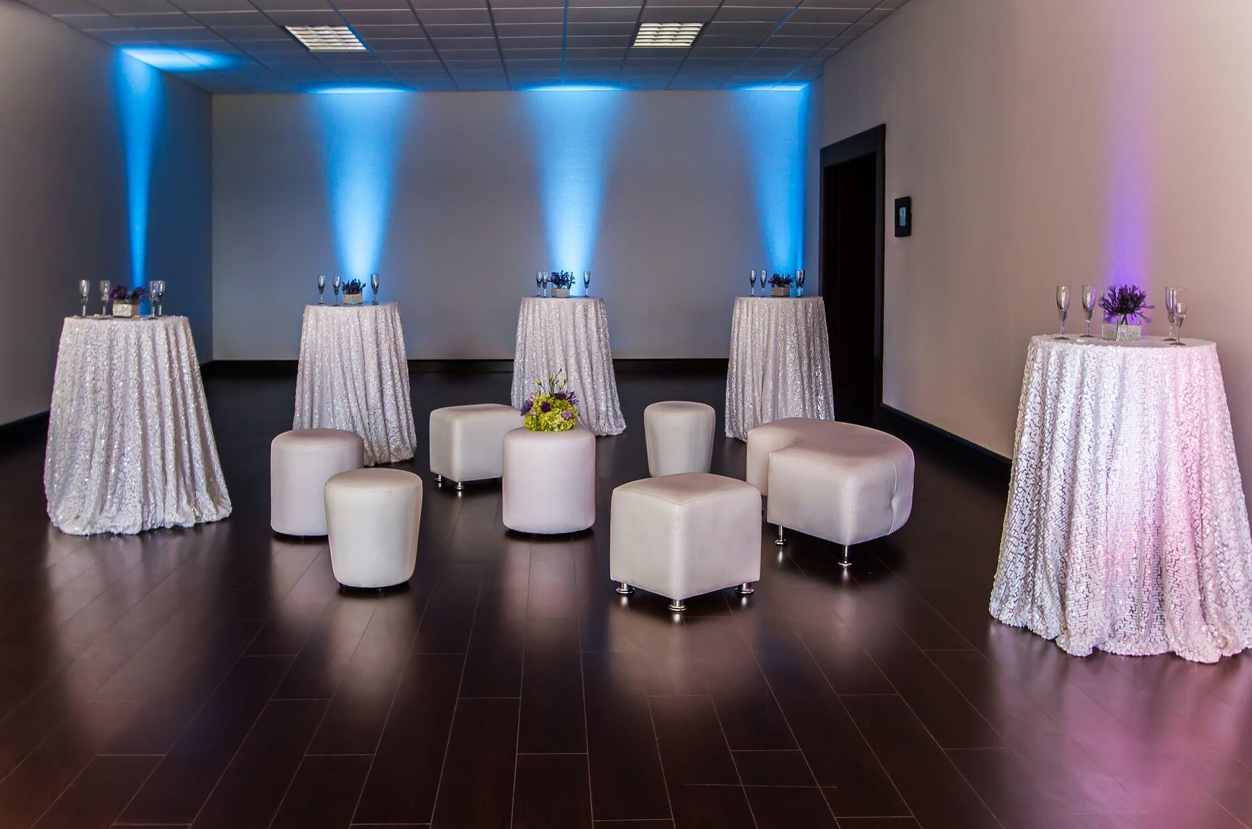 Cocktail tables with small ottoman seating in reception area