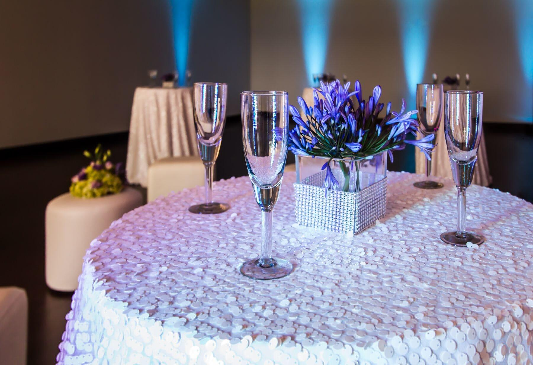 Champagne flutes and floral centerpiece set on cocktail table