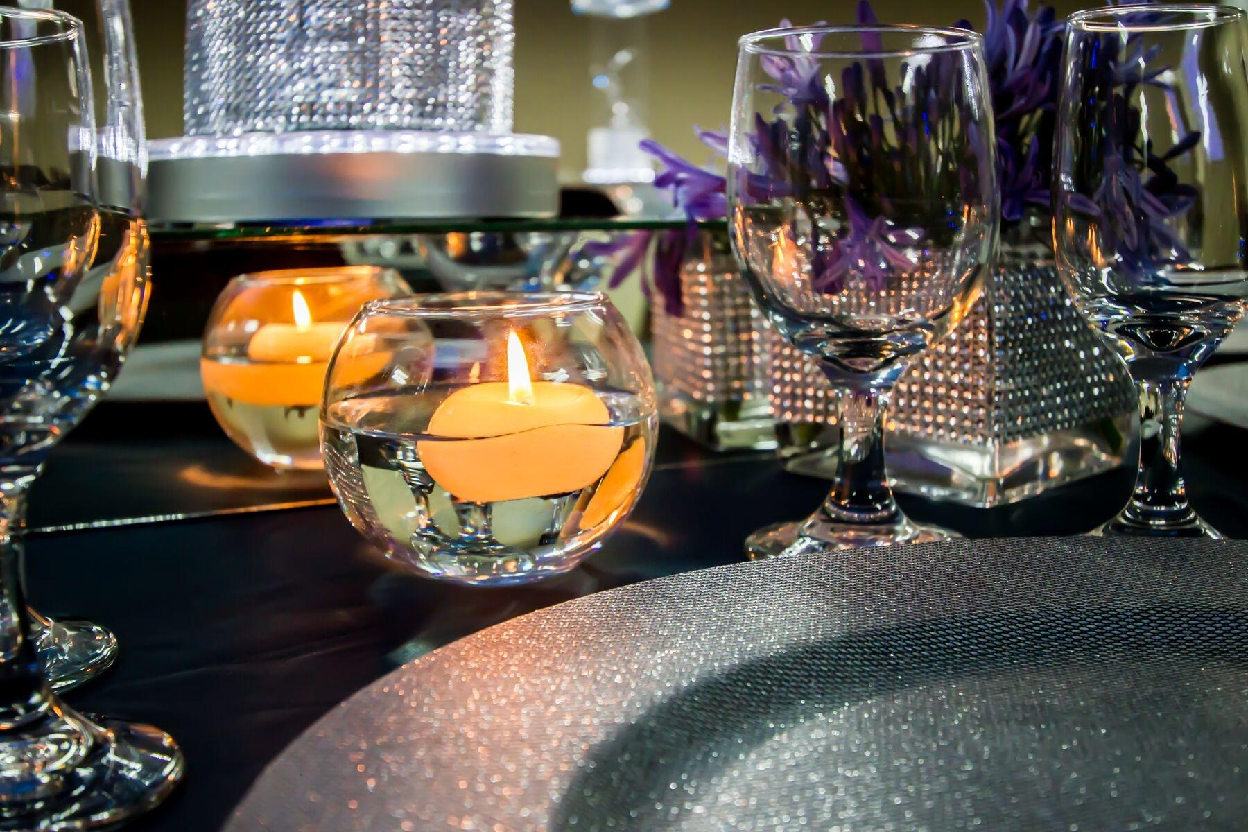 Candle votives and glasses set on banquet table