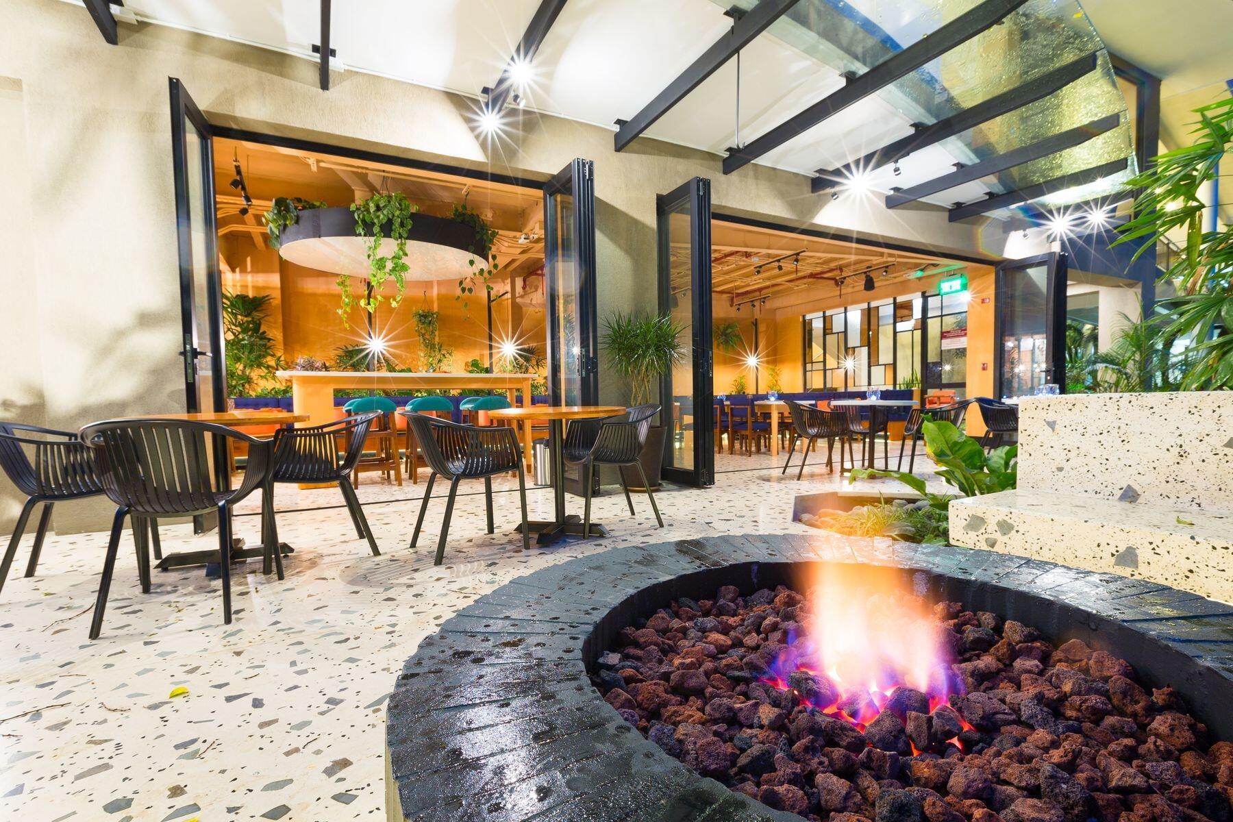 Outdoor fire pit and bistro tables at hotel lounge