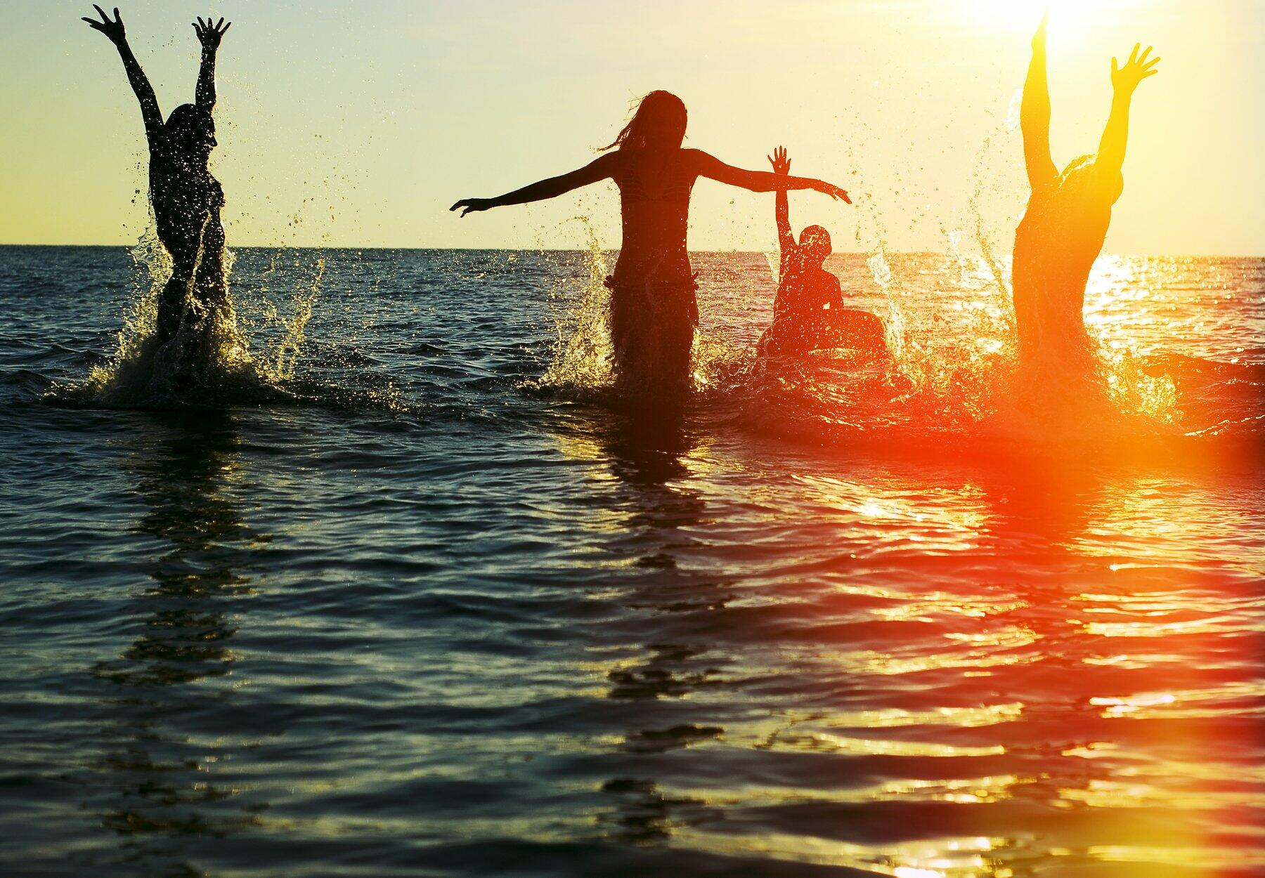 Friends playing in the ocean water at sunset