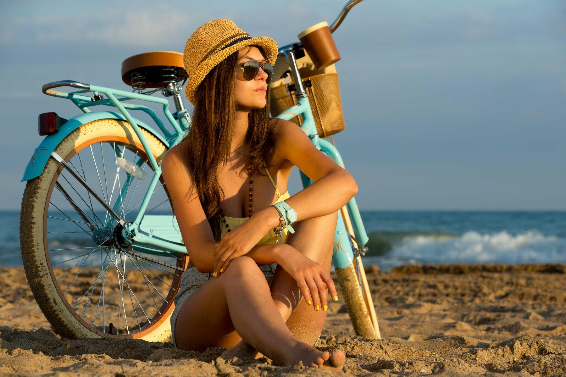 Girl on a beach with her bike