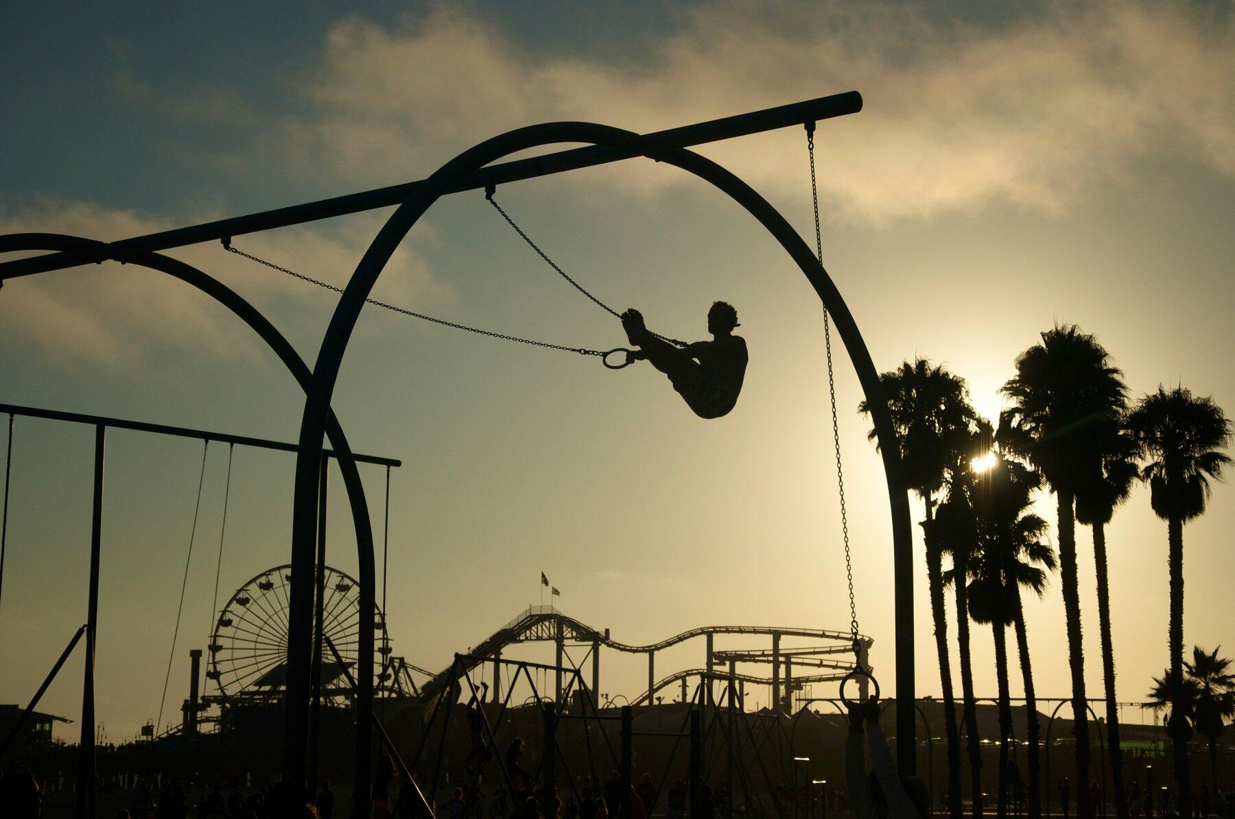Silhouetted person using gymnast rings at Santa Monica Pier