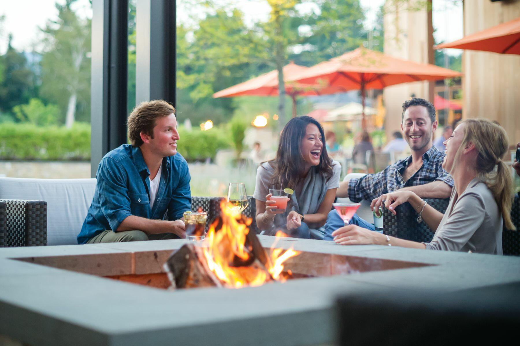 Four friends gathered around a fire pit.