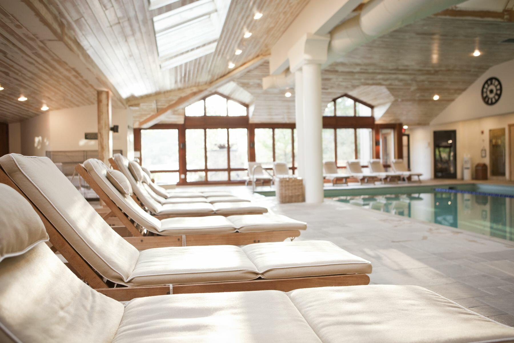 A line of spa chairs along the edge of a spa pool.