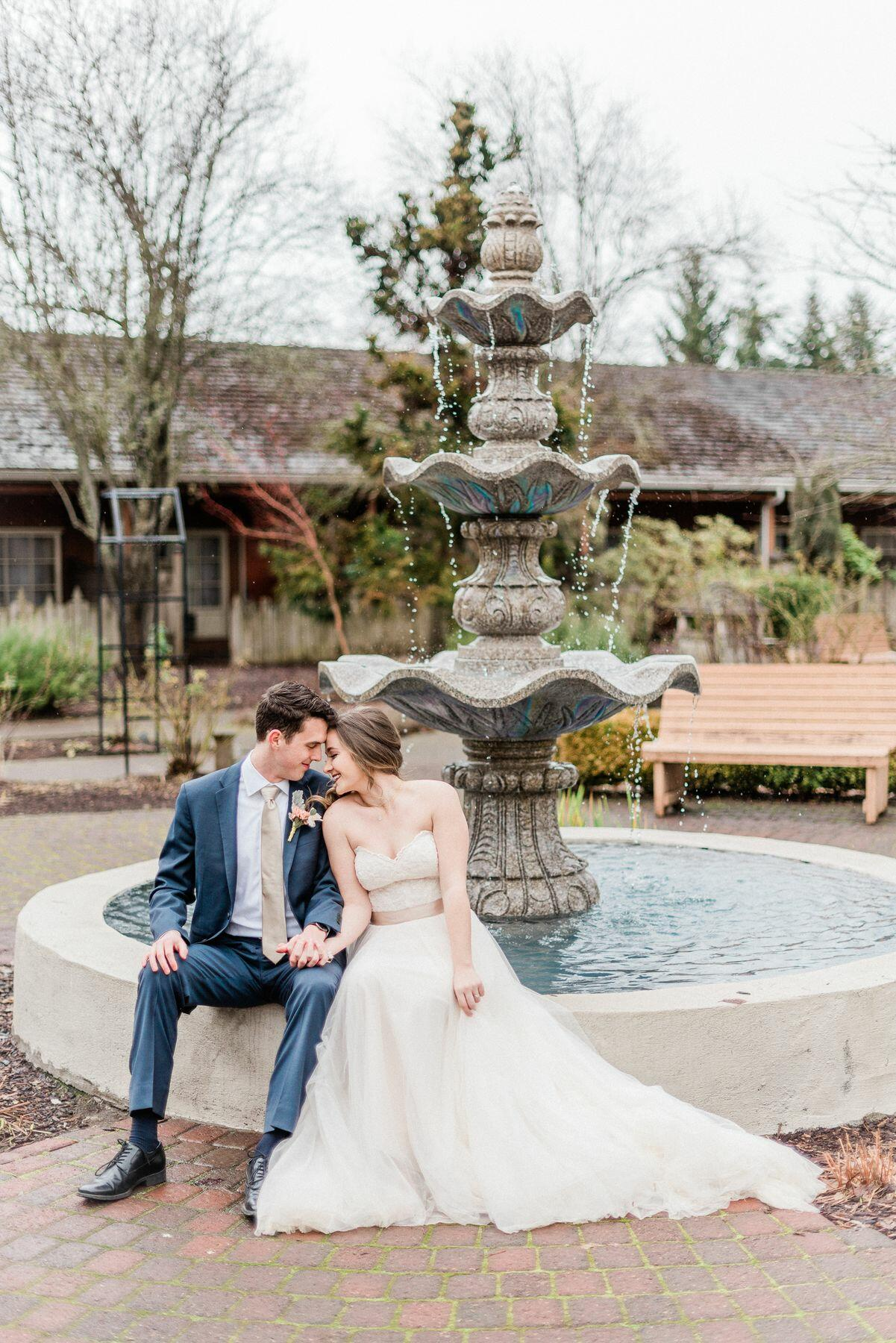 married couple sitting in front of fountain