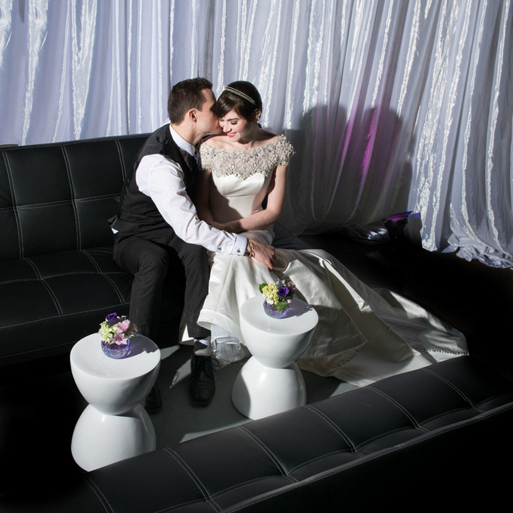 Bride and groom sitting on couch.