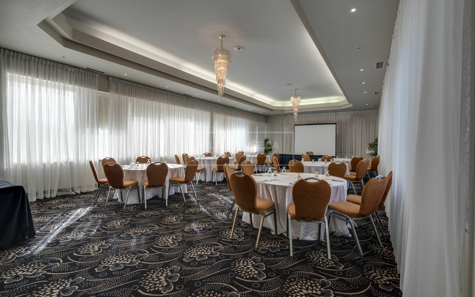 Meeting space set with banquet rounds and chairs.