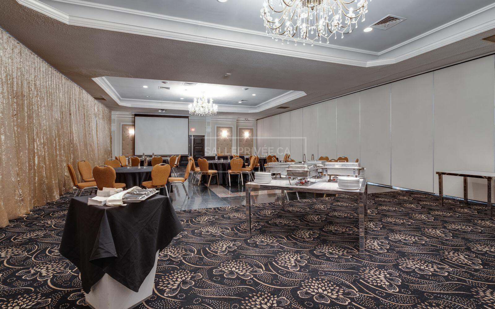 Meeting space set with buffet table and banquet rounds.