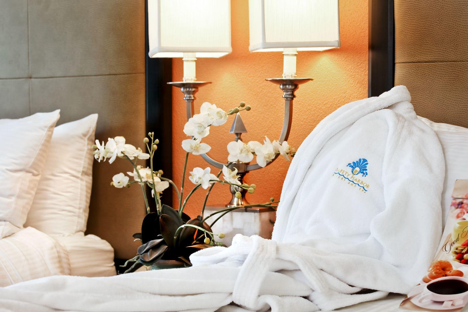 Hotel room with white bathrobe and flowers.