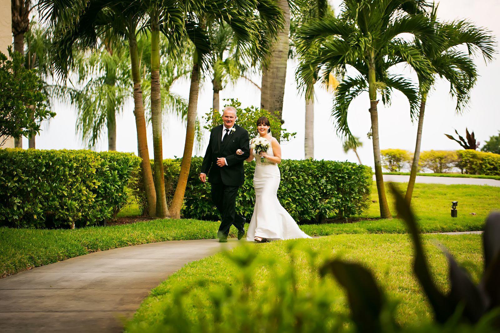Father walking bride across landscape.