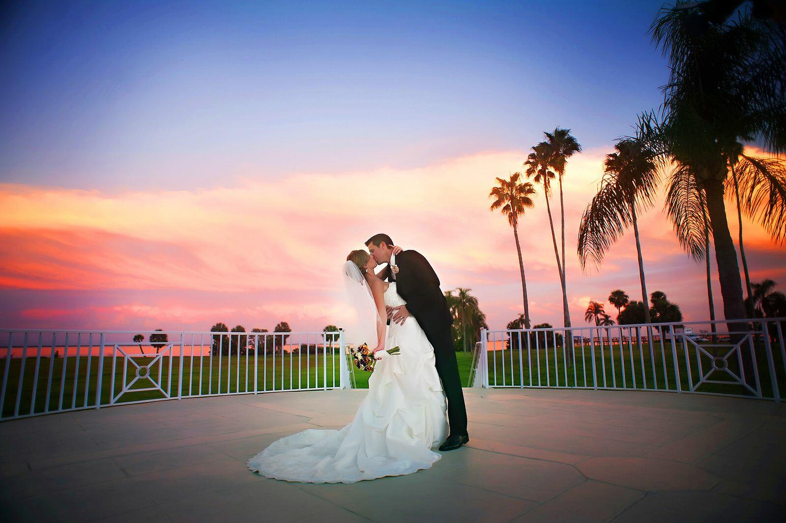 Newlyweds kissing under sunset Tampa Bay.