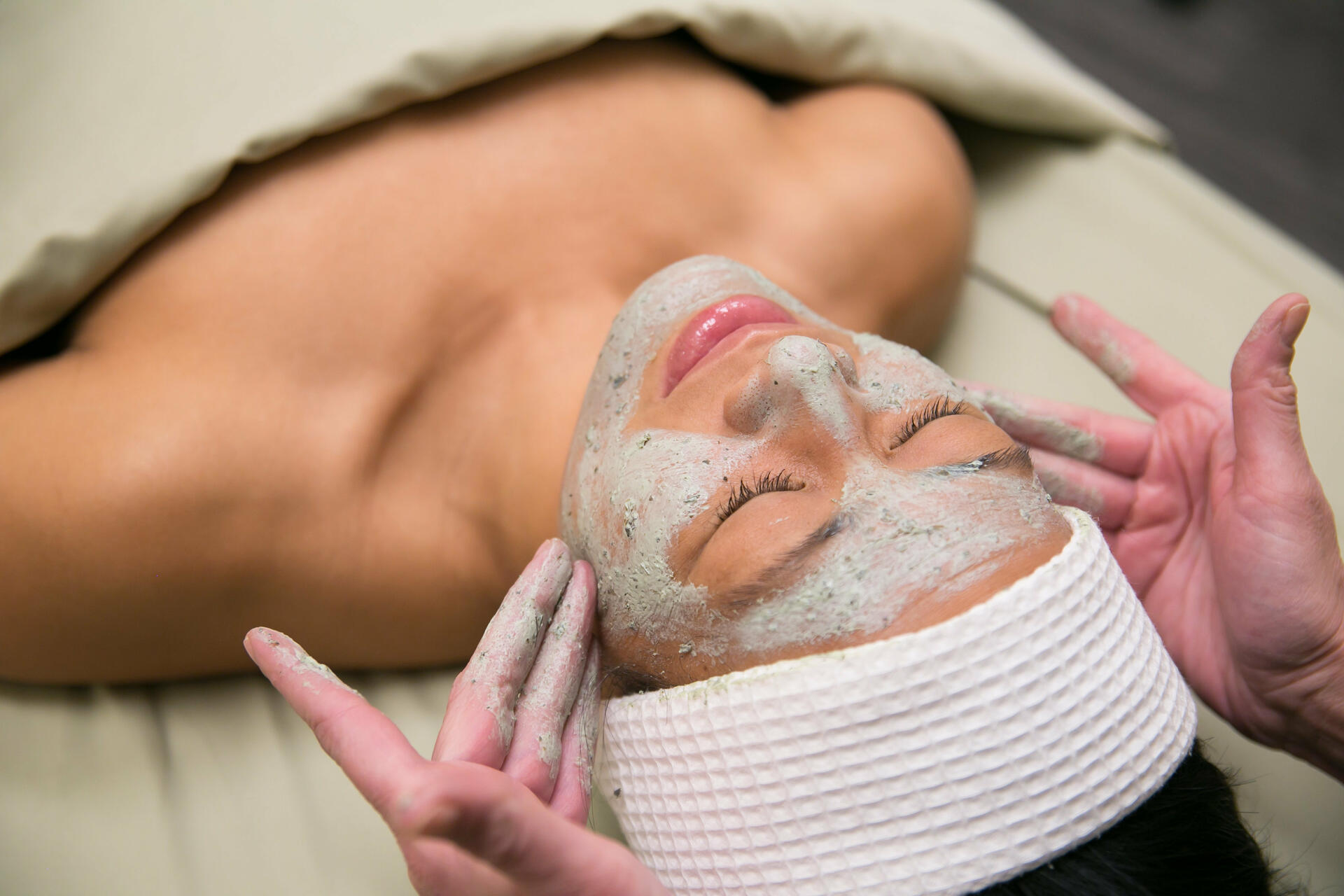 Woman receiving spa facial treatment