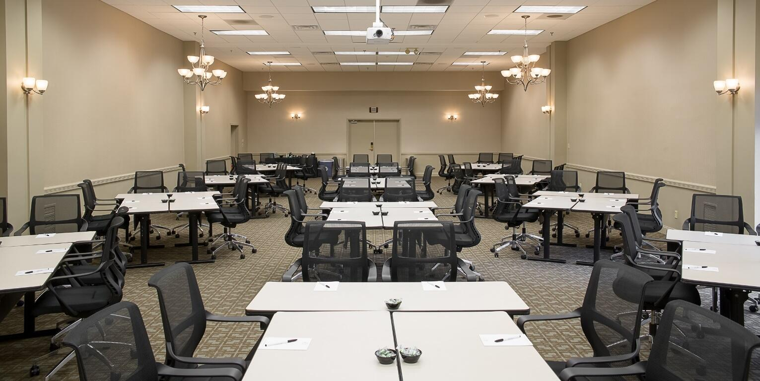 Meeting room with multiple tables and office chairs